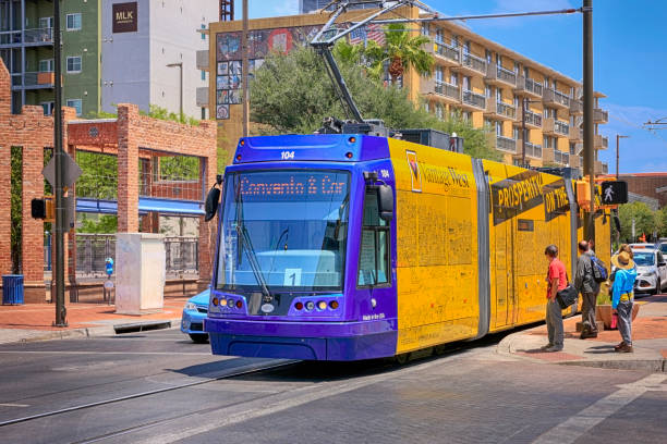 People waiting to cross at an intersection with a passing Street car in downtown Tucson AZ stock photo