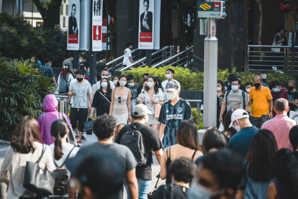People waiting to cross the Orchard Road in Singapore stock photo