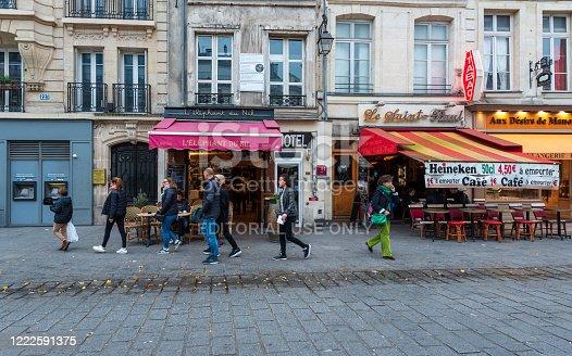 Paris, France -- November 4, 2017. Tourists and Parisiannes walk along Rue St Antoine past bistros and bars.