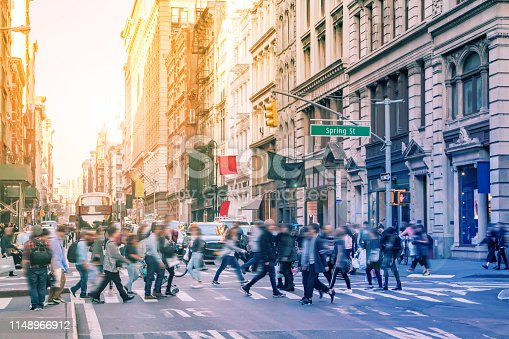 Diverse groups of people walk across the crowded intersection of Broadway and Spring Street in the SoHo neighborhood of Manhattan in New York City with bright sunlight background