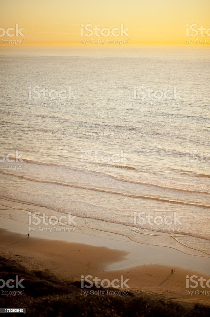 People Walk Along The Beach And Ocean At Sunset stock photo