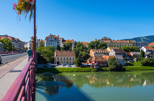 People walk along the Old Bridge or Stari Most over the Drava river in Old city Maribor in Sloveniain