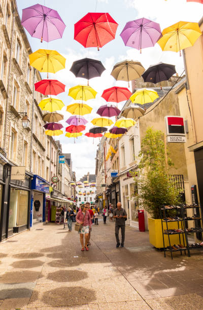 People walk along the pedestrian shopping street under the Umbrellas of Cherbourg. Normandy France Cherbourg-Octeville, France - August 21, 2018: People walk along the pedestrian shopping street under the Umbrellas of Cherbourg. Normandy France cherbourg stock pictures, royalty-free photos & images