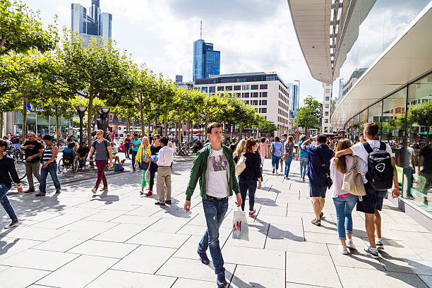 people walk along the Zeil in Frankfurt Frankfurt, Germany - August 9, 2014: people walk along the Zeil in Midday  in Frankfurt, Germany. Since the 19th century it is of the most famous and busiest shopping streets in Germany. town square stock pictures, royalty-free photos & images
