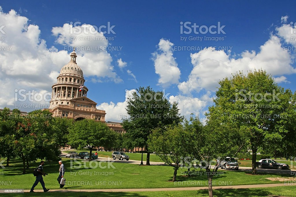 people walk at Texas state capitol stock photo