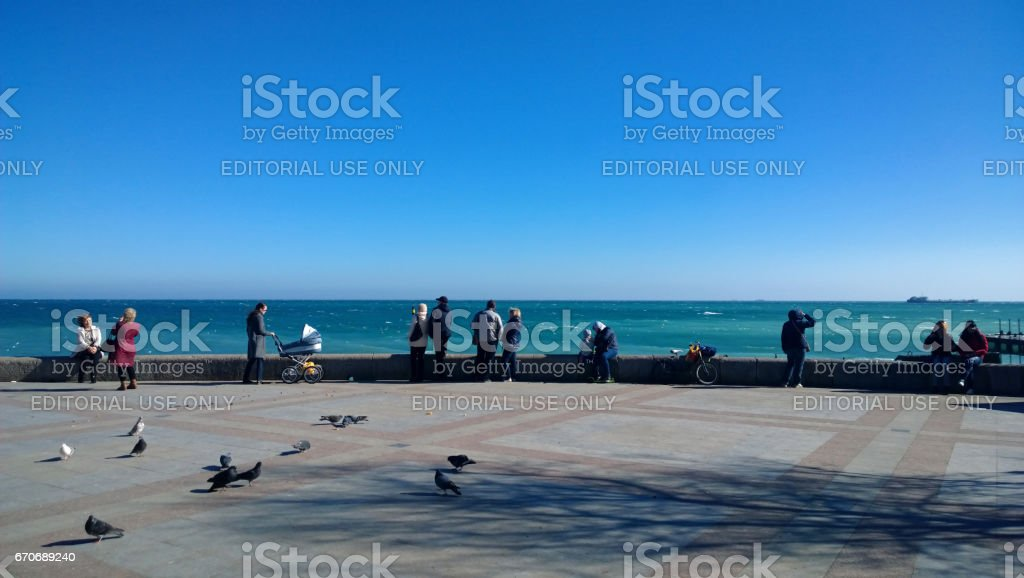 Yalta, Russia - February 2017: People walk in a Sunny winter day on the seafront of Yalta stock photo