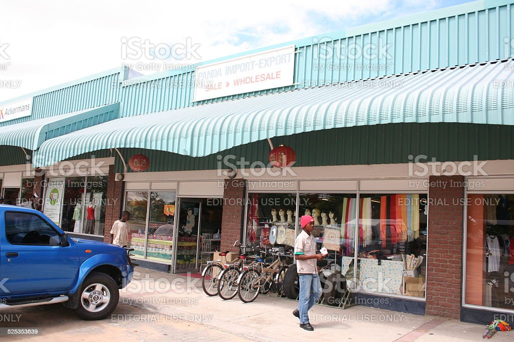 People walk in front of a shop, Rundu, Namibia, Africa stock photo