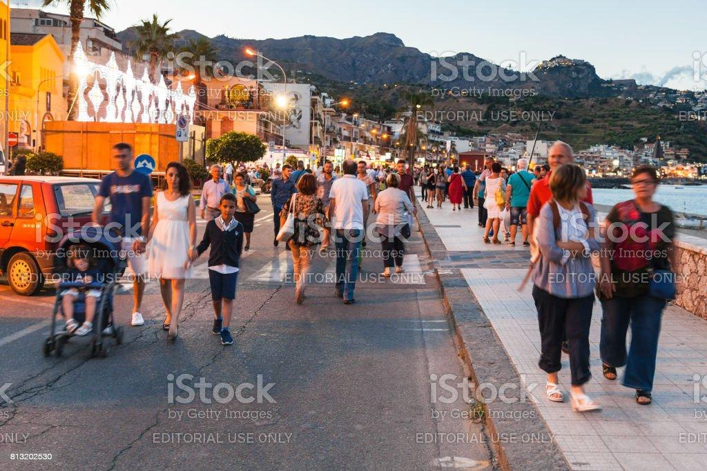 people walk in Giardini Naxos in evening stock photo