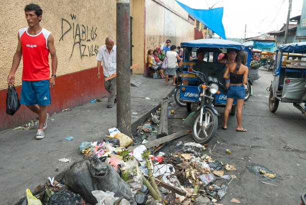 People walk in market area in Belen, Iquitos, Peru. Iquitos, Peru - April 30th, 2010: Unidentified people walk in market area in Belen, Iquitos, Peru. Belen is the biggest slum in Peru and the most polluted district of Iquitos. mercato stock pictures, royalty-free photos & images