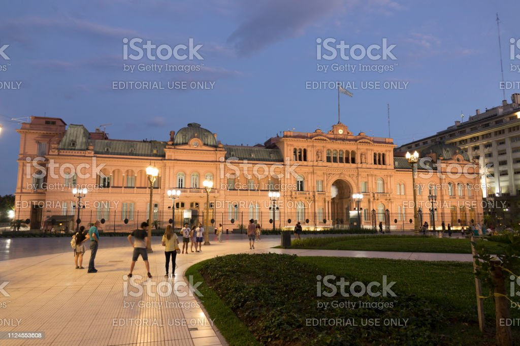 People walk nighttime sidewalk Plaza de Mayo park Presidential Casa Rosada Buenos Aires Argentina stock photo