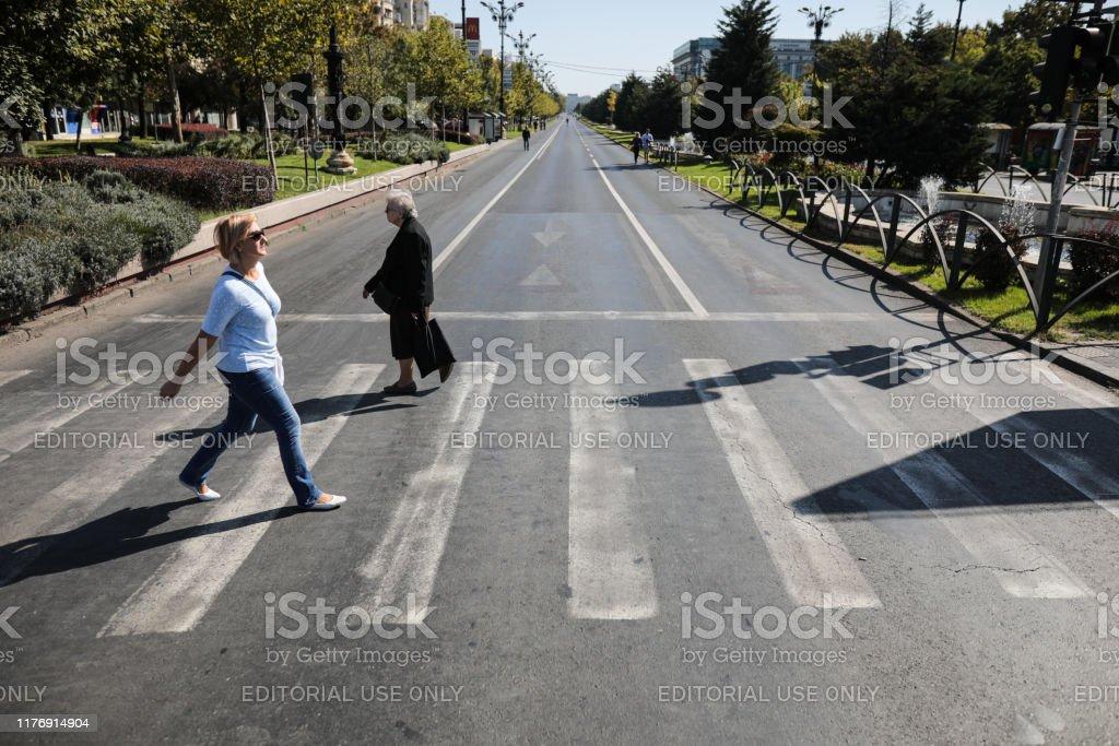 La gente camina en un bulevar vacío (generalmente con mucho tráfico) durante el Día Mundial del Automóvil Libre. - Foto de stock de Accidente de automóvil libre de derechos