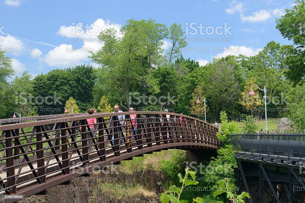 People walk on bridge over Passaic River stock photo