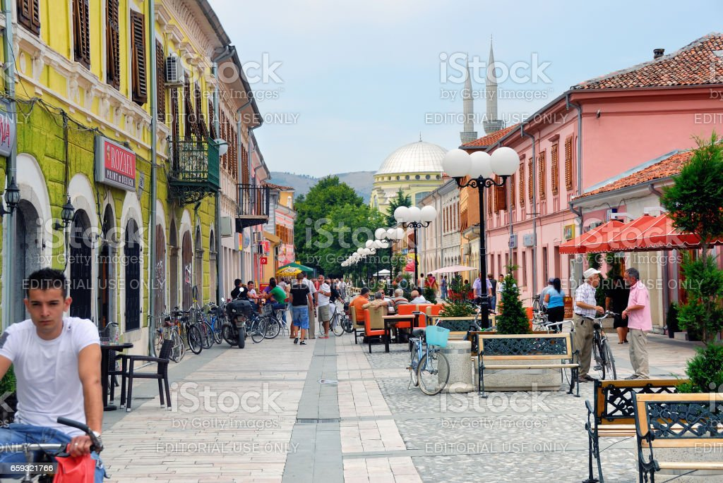 SHKODER, ALBANIA - SEPTEMBER 23, 2013: People walk on he street, Ebu Bekr Mosque on background. Shkodra is one of the oldest places in Albania, as well as an important cultural and economic centre. stock photo