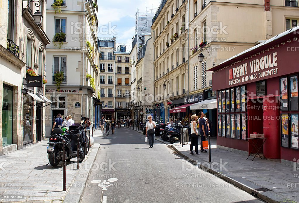 People walk on one of streets of Le Marais Paris, France - July 8, 2016: People walk on one of streets of Le Marais district of Paris. This area are full of artisan boutiques, restaurants, cafes. Adulation Stock Photo