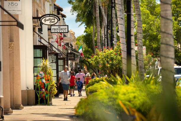 People walk on the sidewalk of Main Street downtown Naples Florida stock photo