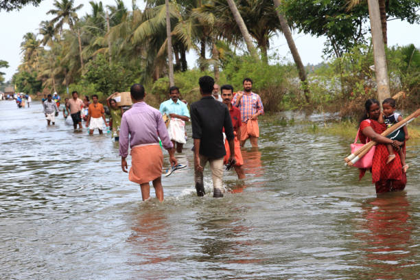 People walk through the flooded roads stock photo