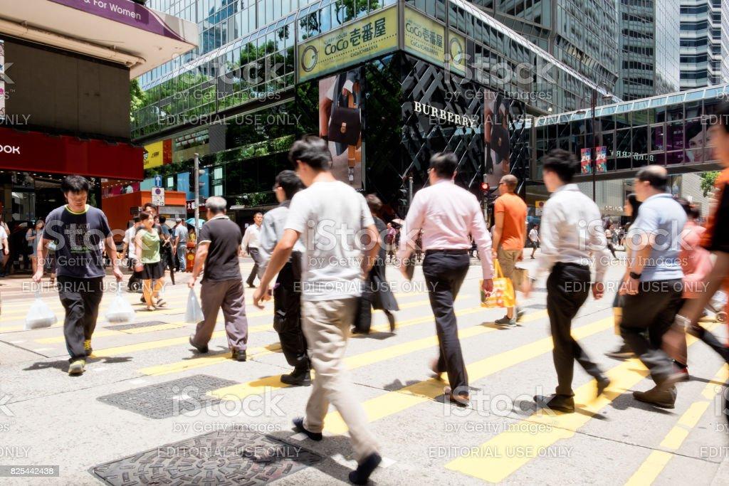 People walking across Canton Road Kowloon, Hong Kong. stock photo