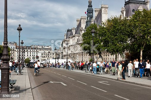 Pont d'Arcole and Place de l'Hotel de Ville in Paris, DSLR shot in sunny summer sunday, many people are visible on walkways, historic buildings are in background