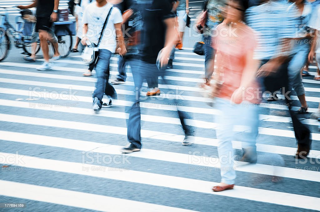 People walking across the crosswalk in a city stock photo