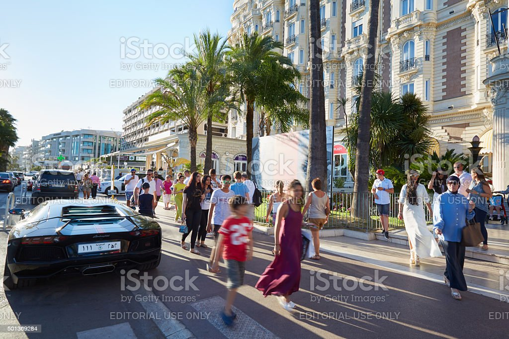 People walking along Croisette boulevard in Cannes in the afternoon stock photo