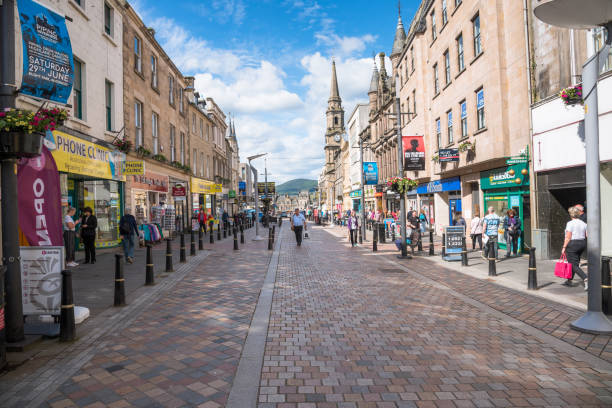 People walking along High Street in central Inverness on a clear summer morning Inverness, UK - June 22, 2019: People strolling along the pedestrianised High Street on a sunny summer morning. Inverness High Street, lined with a fantastic variety of local Scottish stores, is a popular area for shopping. inverness scotland stock pictures, royalty-free photos & images