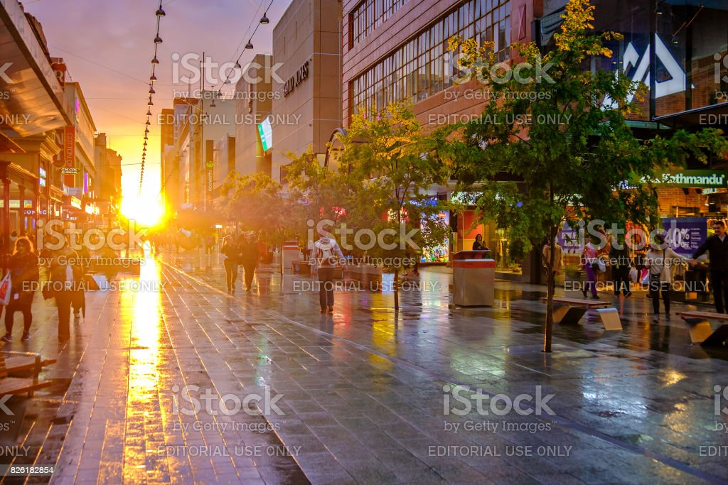 People walking along the Rundle Mall at sunset stock photo