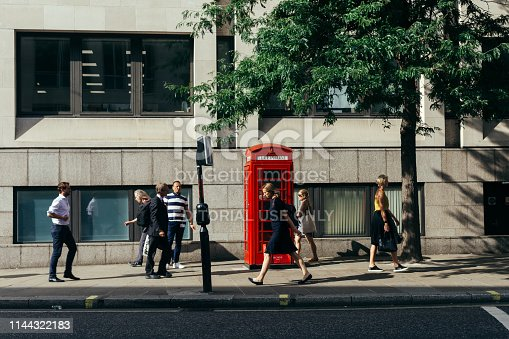 London / UK - July 24, 2018: people passing by the Cheapside street in the City Of London on a warm sunny day. Red telephone box on the background