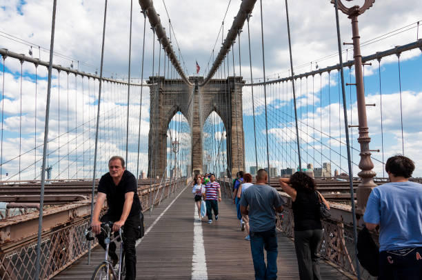 People walking and a cyclist at the Brooklyn Bridge stock photo