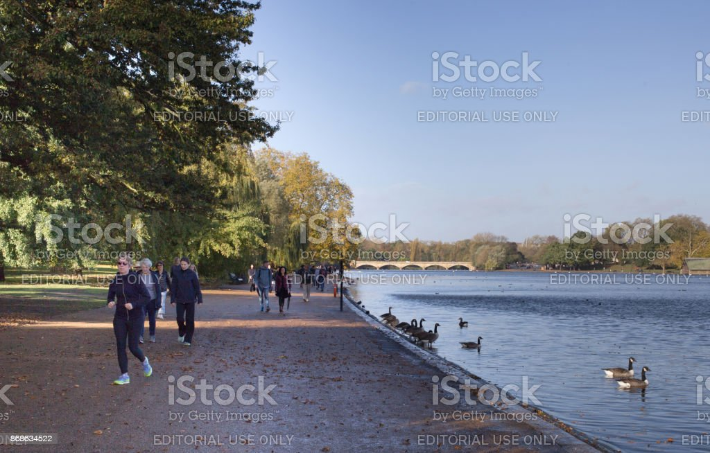 People walking and Jogging along the shorline of The Serpentine Lake in Hyde Park, London, UK stock photo