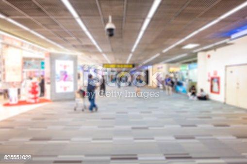istock people walking around duty free shop in airport terminal - blur 825551022