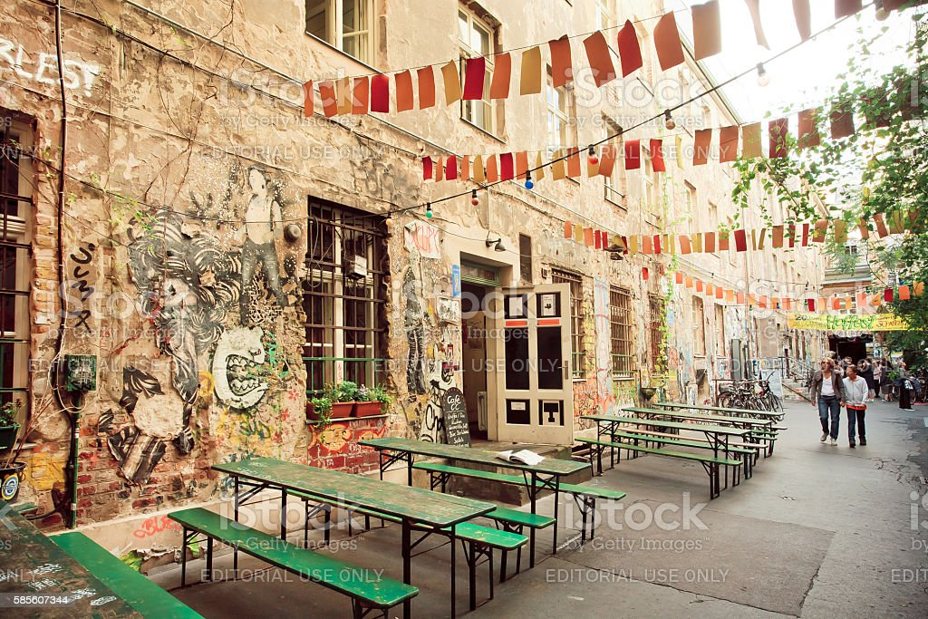 People walking around grunge street cafe and graffiti artwork stock photo
