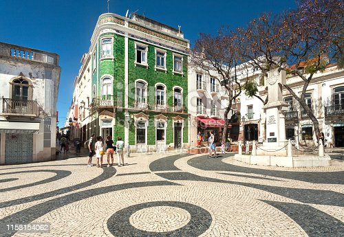 Lagos, Portugal: People walking around historical houses with ceramic tiles walls, at sunny street of Algarve town on 11 May, 2019. Portuguese language has 250 million total speakers