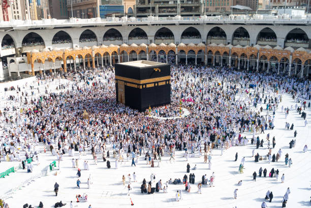 People walking around Holy Kaaba MECCA, SAUDI ARABIA: People walking around Holy Kaaba seven circles in Masjid Al Haram or Grand Mosque of Makkah, making Tawaf. Amazing shots from the top roof floor of the mosque umrah stock pictures, royalty-free photos & images