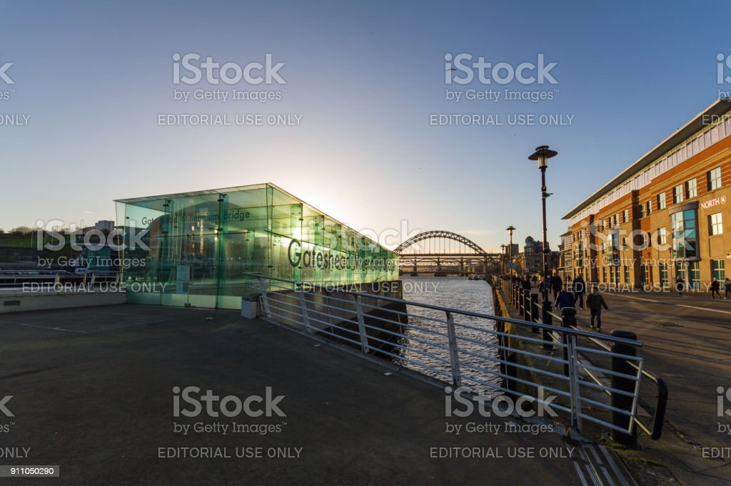 People walking at Newcastle Quayside near the Entrance to the Gateshead Millennium Bridge in the afternoon on New Year's eve stock photo
