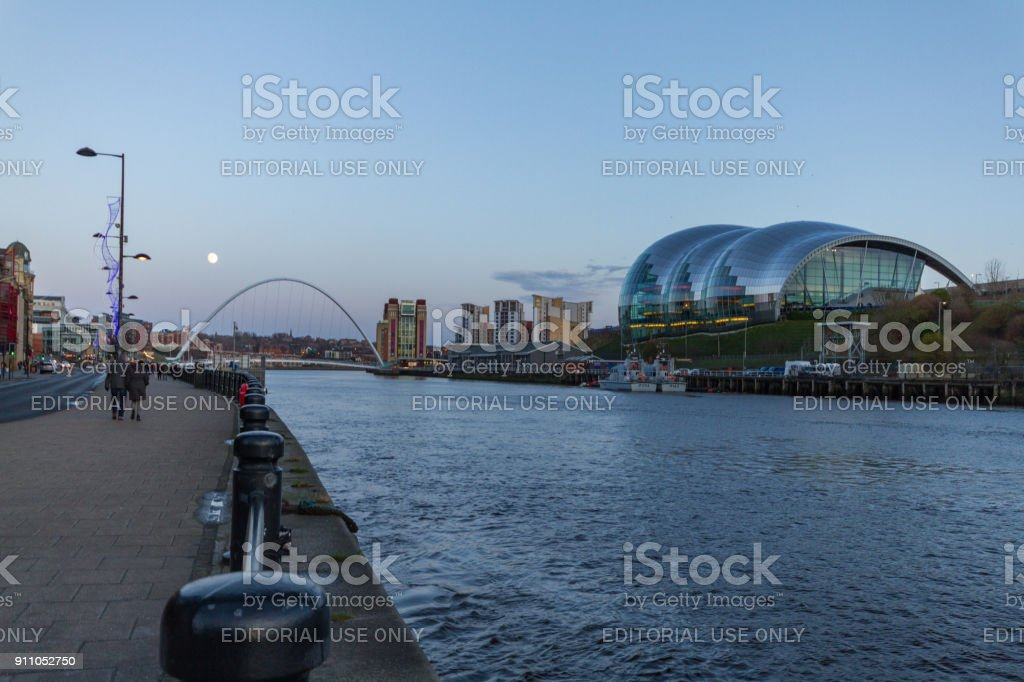 People walking at Newcastle Quayside with Gateshead Millennium Bridge, Sage concert hall and other landmarks in the background at dusk on New Year's eve stock photo