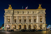 People walking at night in the Place de l´opera (Opera square) next to the Palais Garnier Opera House (Opera du Paris) at Paris city, France. Inaugurated in 1875, it is one of the most famous places in Paris.