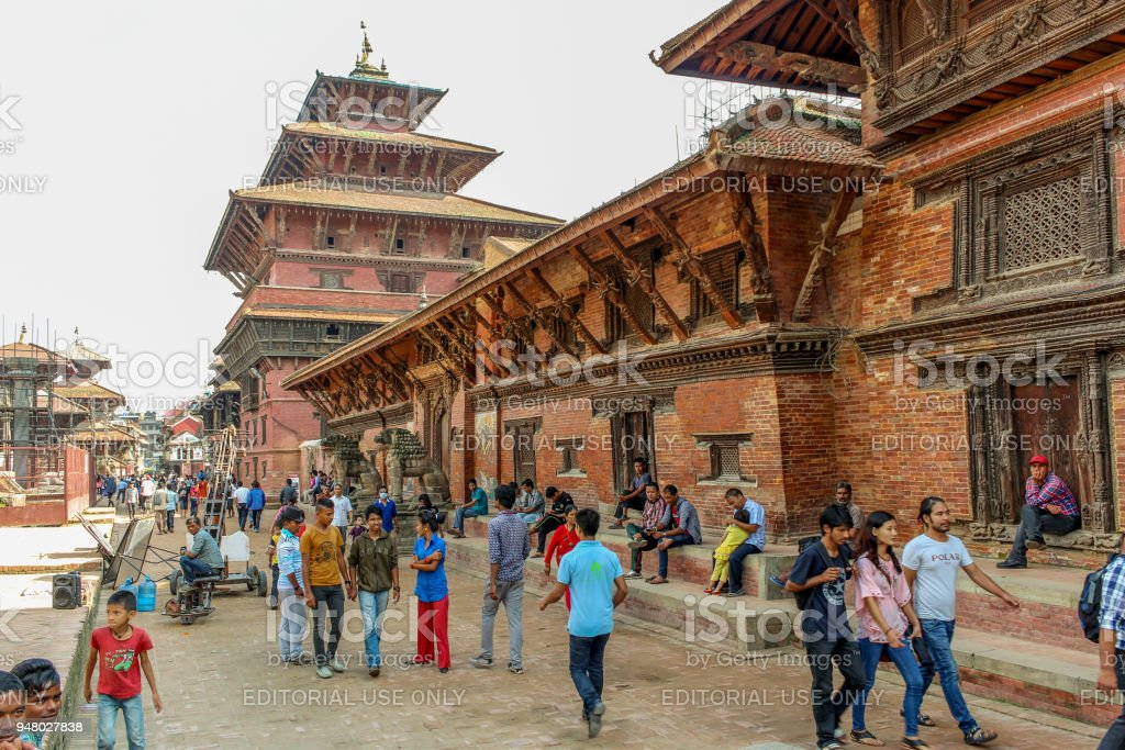 People walking at Patan Durbar Square on a sunny day, Nepal stock photo