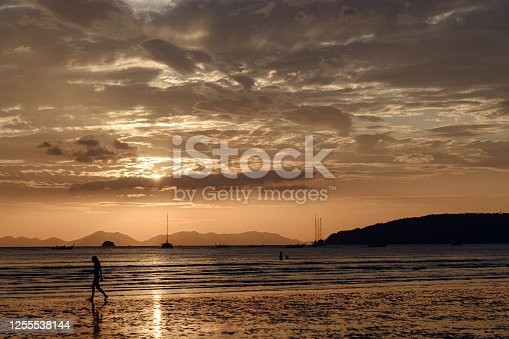 people walking at the beach on beautiful summer sunset.