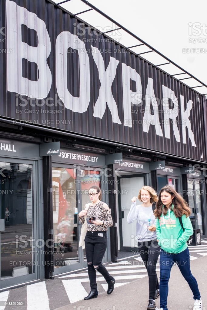 People walking at the BOXPARK, a cool pop up shopping venue with several indie shops and bars in Shoreditch, London, UK. stock photo