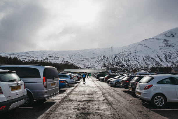 People walking at the car park of Glencoe Mountain Resort, Scotland. Glencoe, Scotland - March 18, 2018: People walking at the car park of Glencoe Mountain Resort. The resort located in the area of outstanding natural beauty on Rannoch Moor, Scotland. north coast 500 stock pictures, royalty-free photos & images