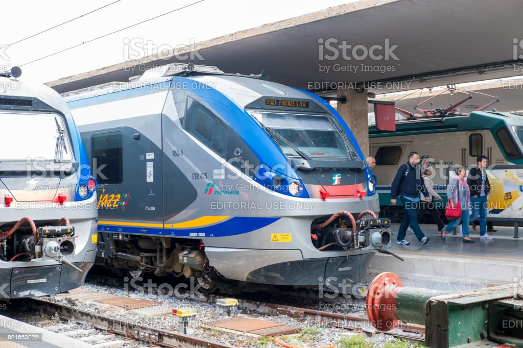 People walking at the platform with Train in Firenze Santa Maria Novella railway station in Florence, Italy. stock photo