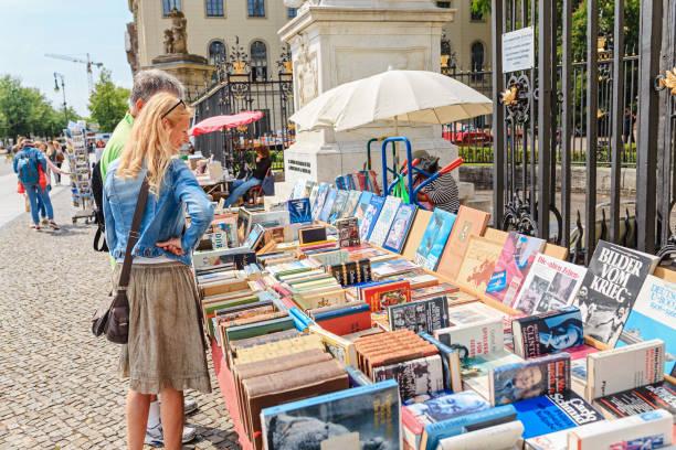 menschen, die auf der gebrauchtbuch-marktmesse in der stadtstraße spazieren gehen - gebrauchte bücher verkaufen stock-fotos und bilder
