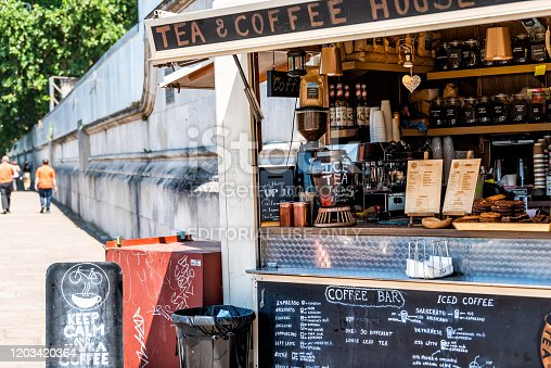 London, UK - June 25, 2018: People walking by coffee or tea small cafe shop in morning by embankment Thames river with menu and food cart