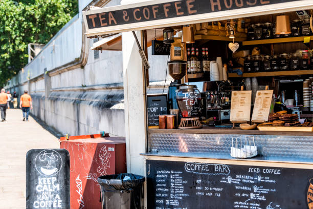 People walking by coffee or tea small cafe shop in morning by embankment Thames river stock photo