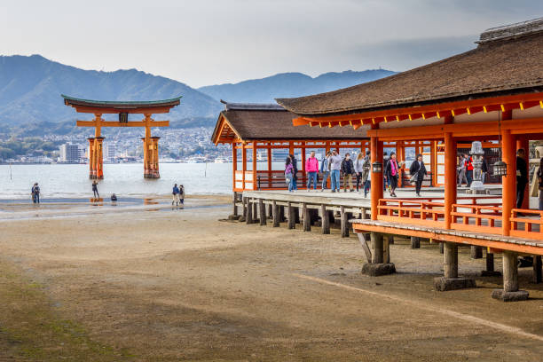 People walking by the Itsukushima Shrine, Miyajima Island, Hiroshima, Japan Miyajima Island, Hiroshima, Japan - 13 April, 2019: People walking by the Itsukushima Shrine. The shrine complex is listed as a UNESCO World Heritage Site. torii gate stock pictures, royalty-free photos & images