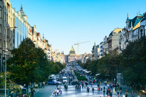 People walking by Wenceslas Square in Prague Prague, Czech Republic - September 30, 2017: People walking by Wenceslas Square, one of the most popular shopping district in Prague. National Museum Building under reconstruction wenceslas square stock pictures, royalty-free photos & images