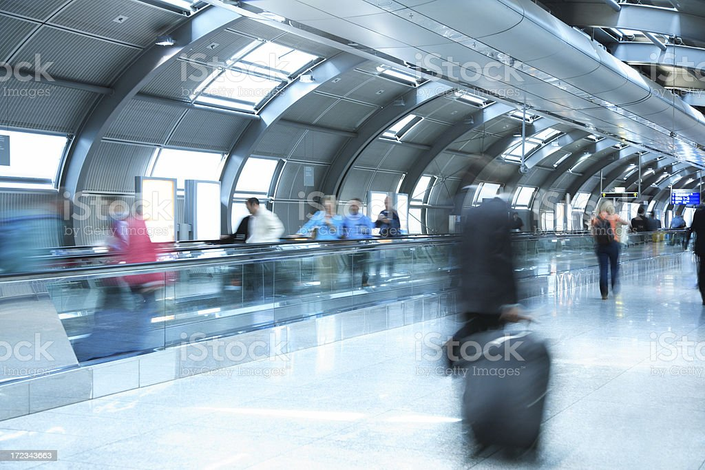 People Walking in Airport Tunnel, Pulling Luggage, Blurred Motion stock photo