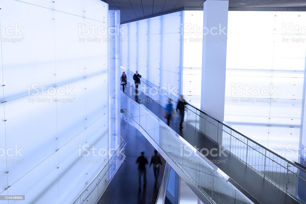 People walking in different direction in commercial building stock photo
