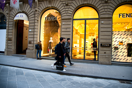 People walking in front Fendi window display in Florence, Tuscany, Italy