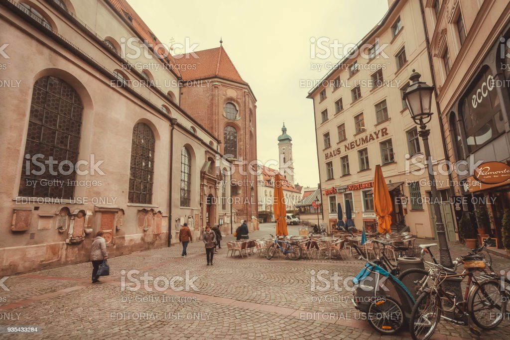 People walking in historical city with old buildings, stores and...